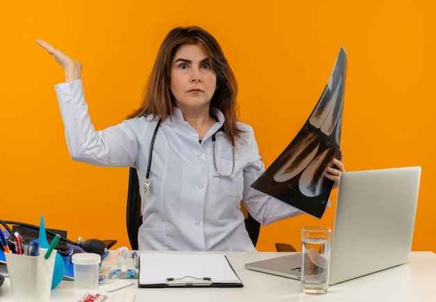 Confused middle-aged female doctor wearing medical robe with stethoscope sitting at desk work on laptop with medical tools holding x-ray and raising hand on isolated orange wall