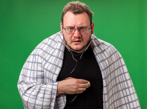 Confused middle-aged ill male wrapped in plaid listening to his own heartbeat isolated on green wall