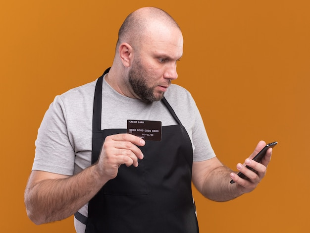 Confused middle-aged male barber in uniform holding credit card and looking at phone in his hand isolated on orange wall