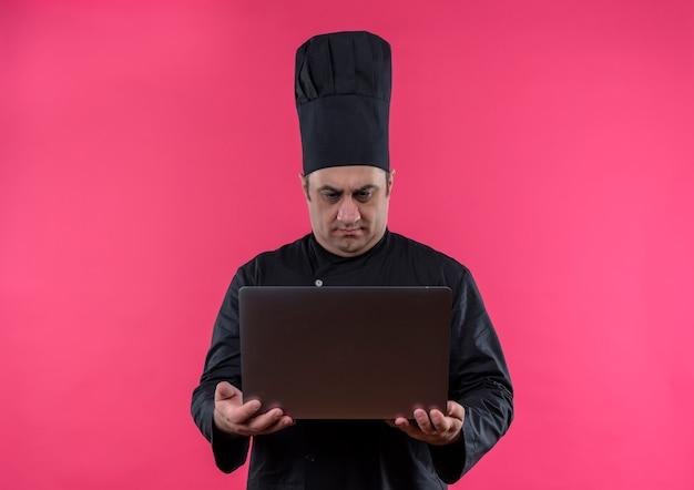 Смущенный мужчина-повар средних лет в униформе шеф-повара смотрит в ноутбук в руке на изолированной розовой стене с копией пространства