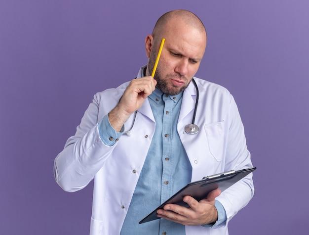 紫の壁に分離された鉛筆で頭に触れるクリップボードを保持し、医療ローブと聴診器を身に着けている混乱した中年男性医師