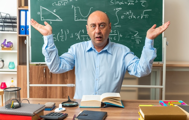 Insegnante maschio di mezza età confuso si siede al tavolo con gli strumenti della scuola che allargano le mani in classe