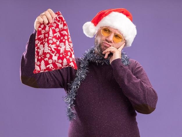 サンタの帽子と見掛け倒しのガーランドを首にかけて、紫色の壁で隔離されたあごに手を置いてクリスマスギフト袋を持って見ている混乱した中年男性