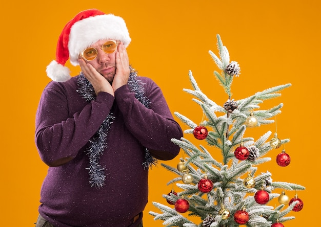 Смущенный мужчина средних лет в новогодней шапке и мишурной гирлянде на шее в очках стоит возле украшенной елки, держа руки на лице, глядя в камеру, изолированную на оранжевом фоне