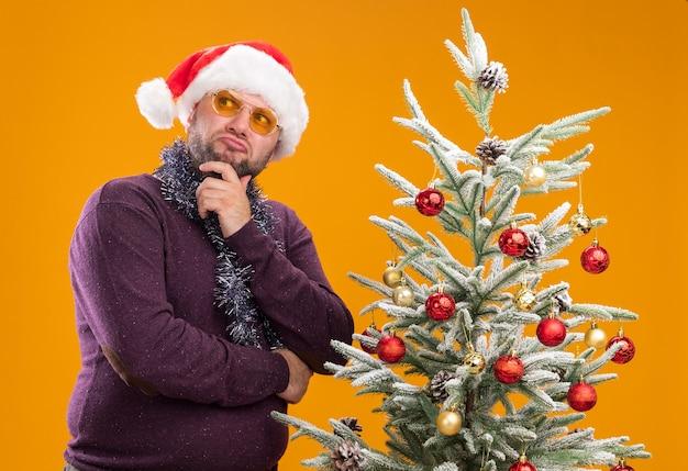 Смущенный мужчина средних лет в новогодней шапке и мишурной гирлянде на шее в очках стоит возле украшенной елки