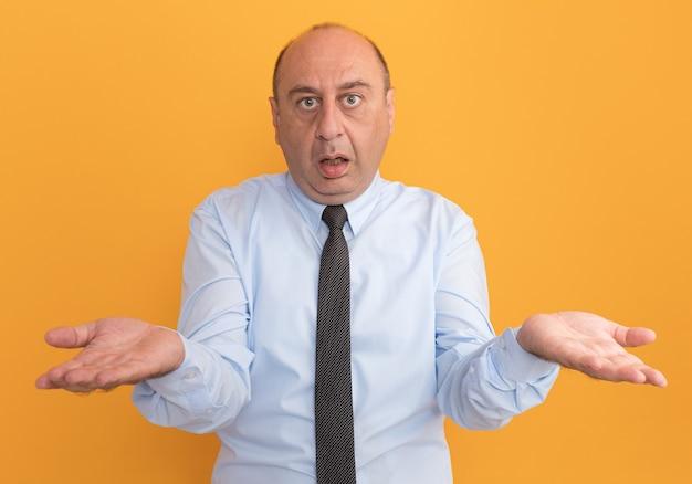 オレンジ色の壁に分離された手を広げてネクタイと白いtシャツを着て混乱した中年男性