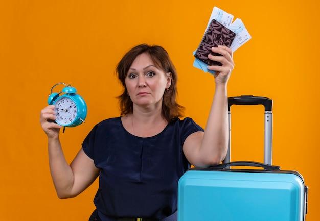 Confuso viaggiatore di mezza età donna che tiene portafoglio e biglietti con sveglia mettendo la mano sulla valigia sul muro arancione isolato