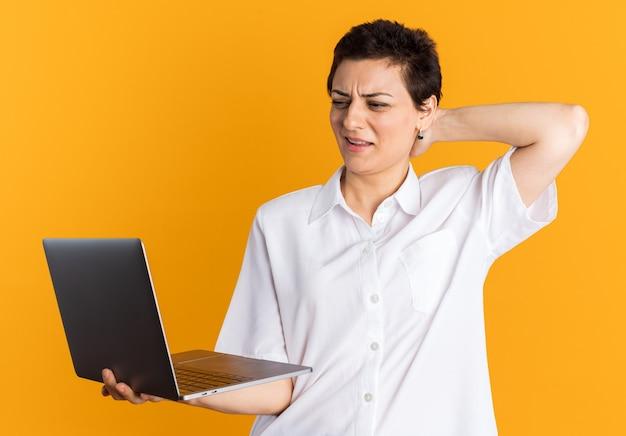 Donna di mezza età confusa che tiene e guarda il laptop tenendo la mano dietro la testa