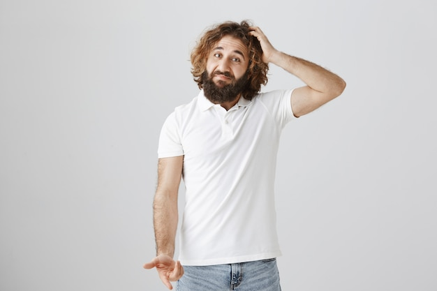 Confused middle-eastern man shrugging and scratch head indecisive