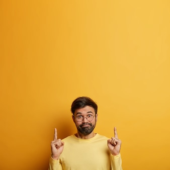 Confused millennial unshaven male points fore fingers above, discusses promotion deal, has hesitant expression, dressed in yellow sweater, expresses wonder and choice, copy space for your text