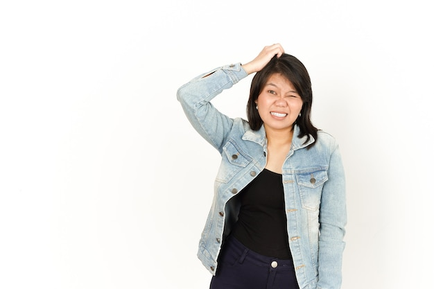 ジーンズのジャケットと白い背景で隔離の黒いシャツを着ている美しいアジアの女性の混乱