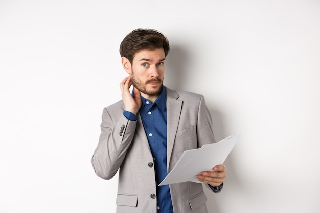Confused office worker in suit scratching beard and look clueless, cant understand document, holding paper with indecisive face, white background.