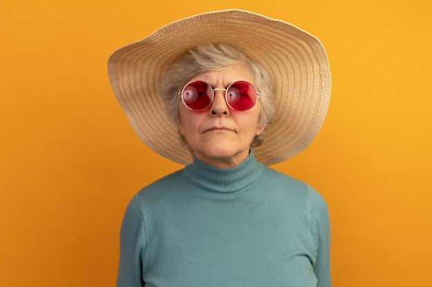Vecchia donna confusa che indossa un maglione blu a collo alto con cappello da spiaggia e occhiali da sole isolati su una parete arancione