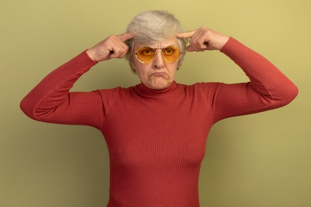 Confused old woman wearing red turtleneck sweater and sunglasses looking straight doing think gesture isolated on olive green wall