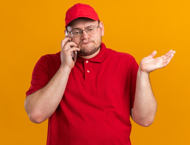 Confuso sovrappeso giovane fattorino in occhiali ottici parlando al telefono isolato sulla parete arancione con spazio di copia