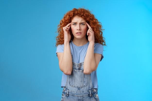 混乱したパニックに陥った若い苦しめられた赤毛の巻き毛のガールフレンドは、タッチテンプルを眉をひそめています。