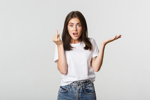 Confused and pissed-off brunette girl arguing about wedding, showing finger without ring.