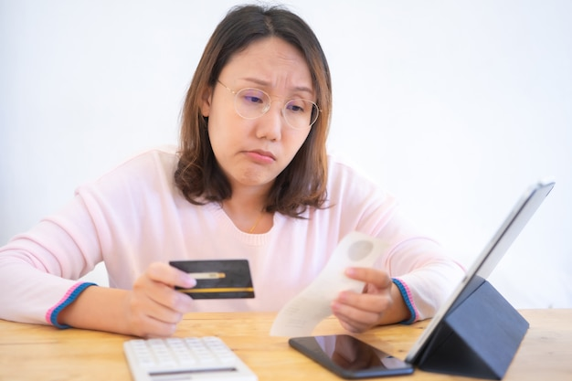 Confused portrait young woman holding credit cards having problem online payment