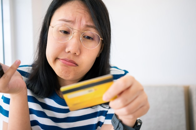 Confused portrait of young woman holding credit cards having problem online payment