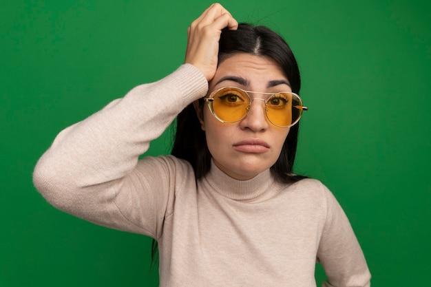 Смущенная симпатичная брюнетка кавказская девушка в солнцезащитных очках кладет руку на голову и смотрит в камеру на зеленом