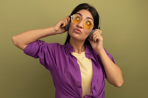 Confused pretty brunette caucasian girl in sun glasses with headphones looks up on olive green