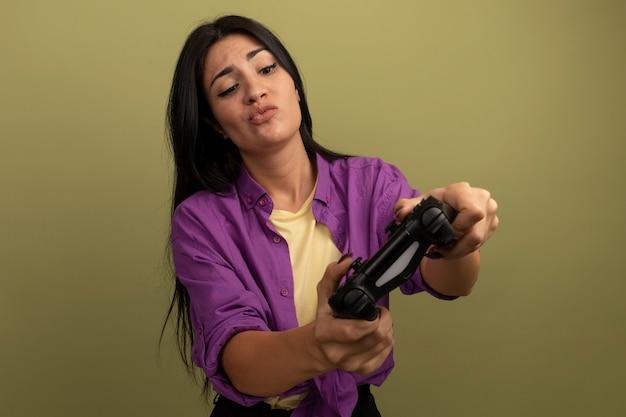 Смущенная симпатичная брюнетка женщина держит и смотрит на игровой контроллер, изолированный на оливково-зеленой стене