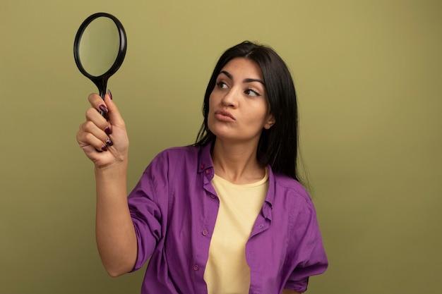 La donna castana graziosa confusa tiene ed esamina la lente d'ingrandimento isolata sulla parete verde oliva