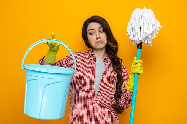 Confused pretty caucasian cleaner woman with rubber gloves holding and looking at bucket and keeping mop