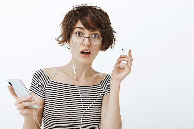 Confused pretty woman in glasses take-off earphone to hear something, holding smartphone