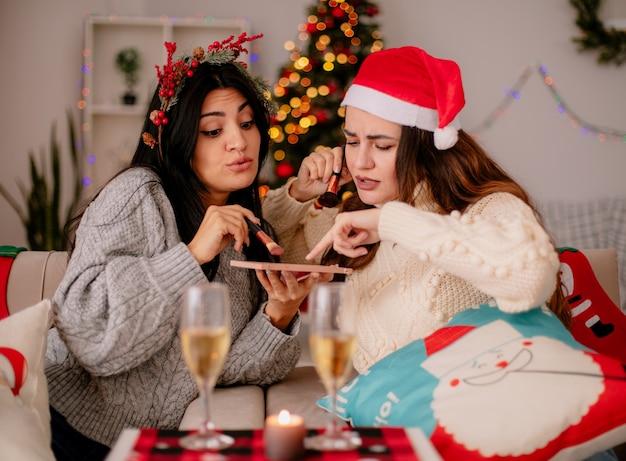 Смущенные симпатичные молодые девушки в новогодней шапке держат кисти для пудры и смотрят на контурную палитру пудры, сидя на креслах и наслаждаясь рождеством дома
