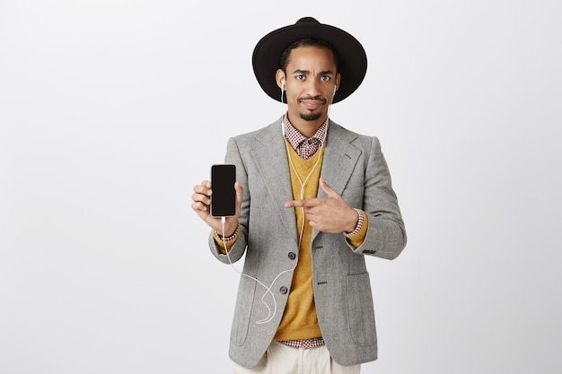 Confused and puzzled african-american guy in suit pointing finger at mobile phone with skeptical expression