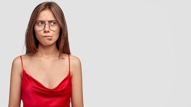 Смущенная озадаченная брюнетка молодая женщина позирует у белой стены