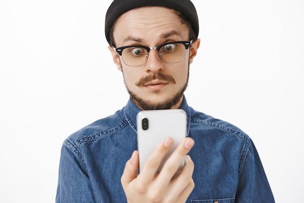 Bel ragazzo europeo confuso e perplesso con barba e baffi in occhiali e beanine hipster alla moda che solleva le sopracciglia dalla sorpresa e fissa lo schermo dello smartphone scioccato e stordito