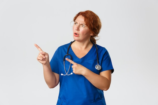 Confused and puzzled middle-aged redhead nurse, doctor cant understand what happening, looking clueless and pointing upper left corner.