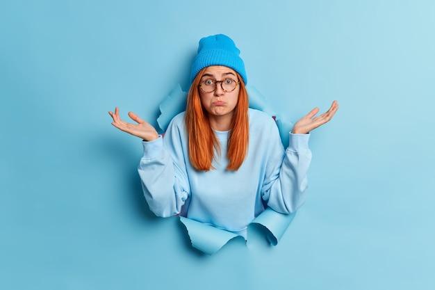 Смущенная озадаченная рыжеволосая молодая допрошенная женщина пожимает плечами и разводит ладони боком, ничего не понимая, стоит в разорванной дыре голубой бумажной дыры