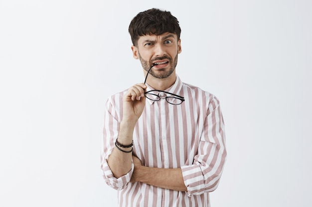 Confused and puzzled stylish bearded guy posing against the white wall with glasses