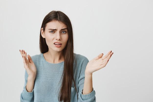 La donna confusa e perplessa alza le mani sgomento