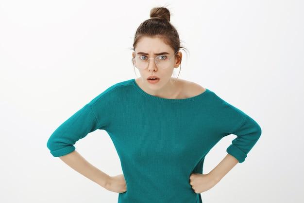 Giovane donna confusa e perplessa con gli occhiali protesa in avanti e guardando più da vicino con la faccia interrogata