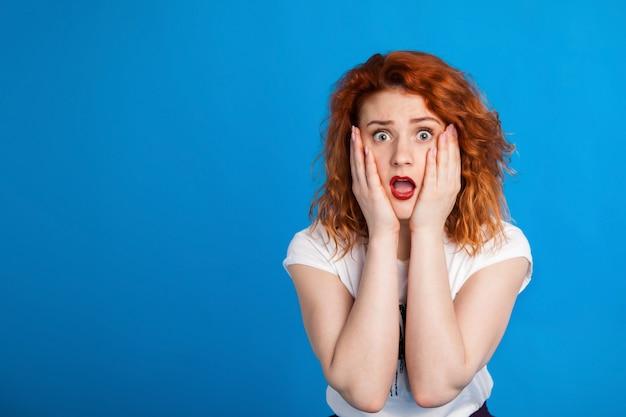 Смущенная рыжеволосая девушка в стиле панк. эмоциональный.