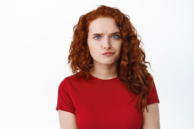 Смущенная рыжая девушка хмурится и смотрит с сомнительным лицом, чувствуя неуверенность или недоумение, задумчиво стоит в красной футболке у белой стены