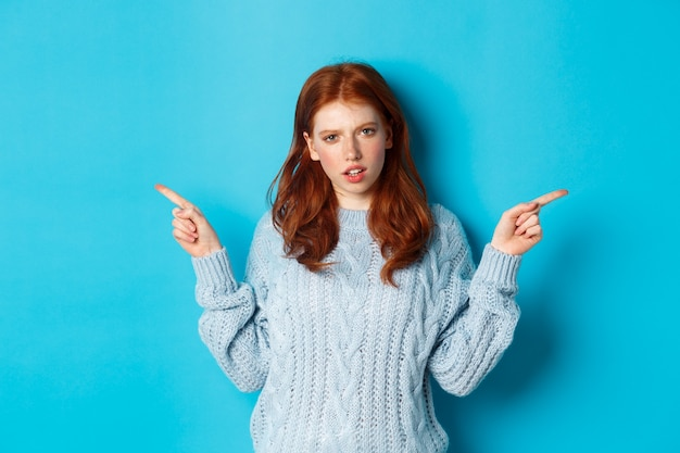 파란색 배경에 서있는 의심스러운 카메라를 쳐다보고 손가락을 옆으로 가리키는 스웨터에 혼란스러운 빨간 머리 소녀
