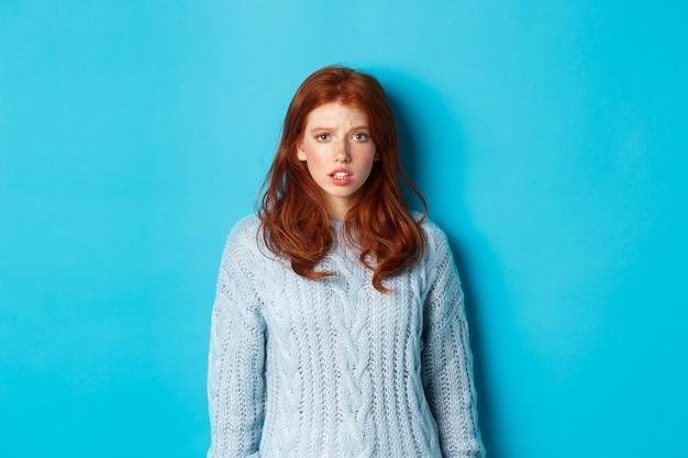 Смущенная рыжая девушка в свитере смотрит в камеру, поднимает бровь и недоумевает, стоя на синем фоне.