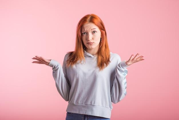Смущенная рыжая девушка пожимает плечами в студии на розовом фоне