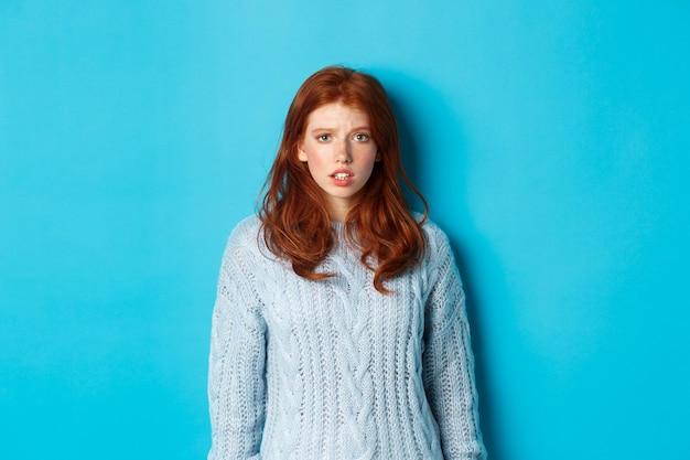 Confused redhead girl in sweater staring at camera, raising eyebrow and feeling puzzled, standing over blue background.