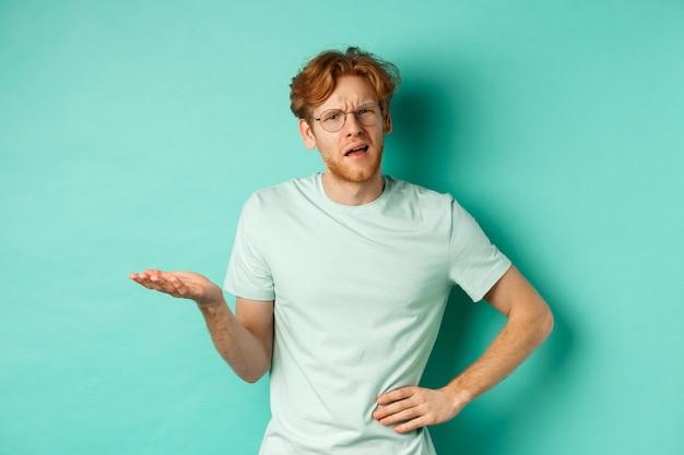 何かを理解しようとしている混乱した赤毛の男、無知に目を細めて片手を伸ばし、困惑しているように見え、ミントの背景の上に立っている