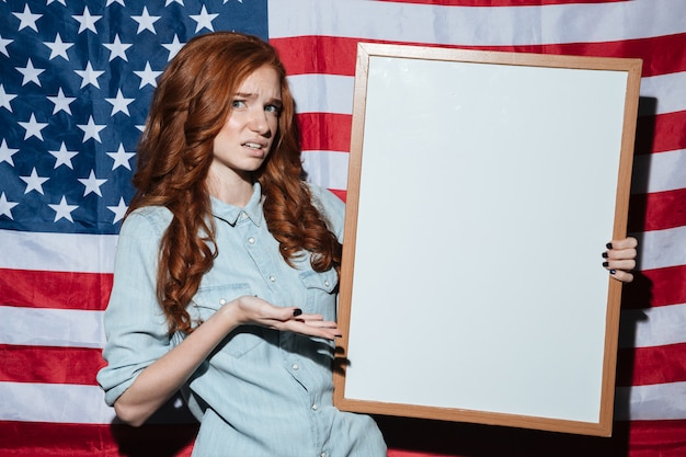 Confused redhead young lady holding copyspace board