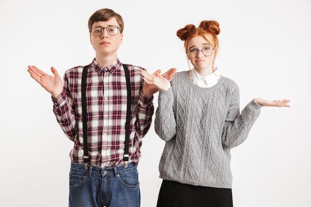 混乱している学校のオタクのカップルが肩をすくめて