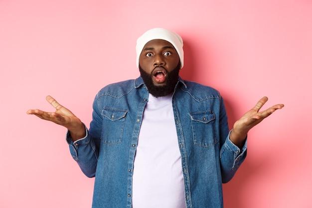 L'uomo afroamericano confuso e scioccato allargò le mani lateralmente e lasciò cadere la mascella, fissando con stupore e stupore la telecamera, in piedi su sfondo rosa senza tracce