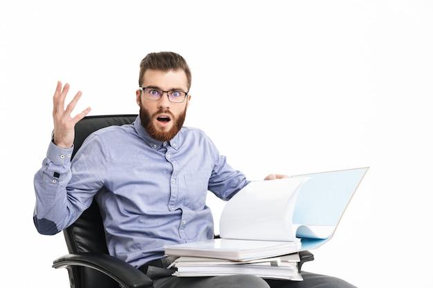 Смущенный шокированный бородатый элегантный мужчина в очках сидит на кресле с папками и смотрит