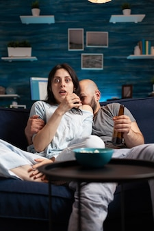 Confused shocked couple watching tv movie at night and eating popcorn